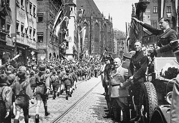 "Baldur von Schirach (saluting), leader of the Hitler Youth, and Julius Streicher (in light-colored jacket), editor of the antisemitic newspaper, ""Der Stuermer,"" review a parade of Hitler Youth in Nuremberg. [Photograph #08063]"