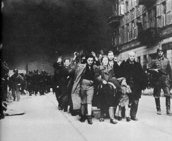 Jews are marched through the streets of the Warsaw ghetto as it burns.